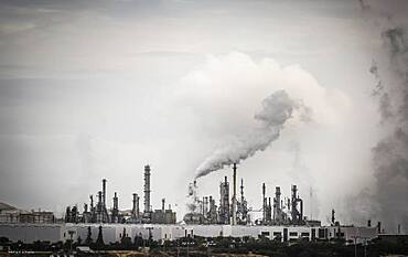 Working industrial plant with smoke stacks billowing smoke into the air