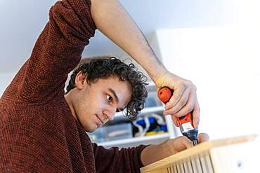 Young man doing DIY in his apartment, assembling a shelf
