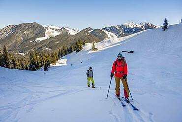 Ski tourers, young woman and man on ski tour to Rosskopf, Mangfall Mountains, Bavarian Prealps, Upper Bavaria, Bavaria, Germany, Europe