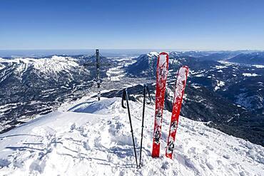Ski stuck in snow, Alpspitz summit with summit cross, ski tour to Alpspitze, view to Garmisch-Patenkirchen, Wetterstein mountains with snow in winter, Garmisch-Partenkirchen, Bavaria, Germany, Europe