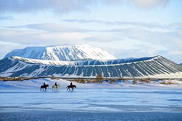 Riders in front of on partly frozen lake Myvatn, volcanoes, Ludent, Hverfjall, Myvatn, Iceland, Europe
