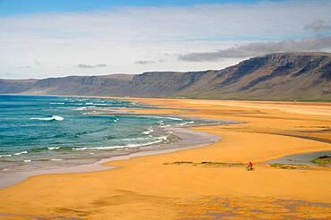 Bicycle on wide sandy beach, waves, Raudarsandur, Westfjords, Iceland, Europe