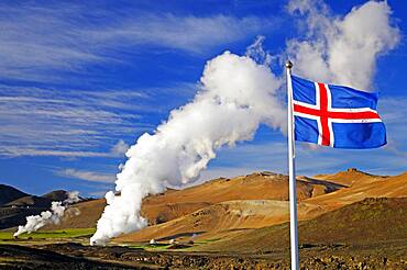Icelandic flag in front of hot steam plumes, geothermal fields in the background, Reykjahlio, Myvatn, Iceland, Europe