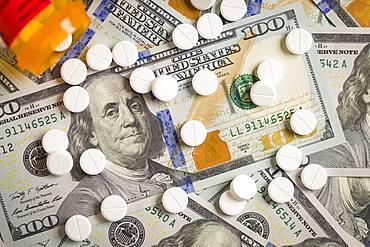 Medicine pills scattered on newly designed U.S. one hundred dollar bills