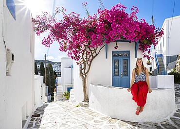 White-blue houses with blooming purple Bougainvillea (Bougainvillea), Young woman with red dress in the old town of Lefkes, Paros, Cyclades, Greece, Europe