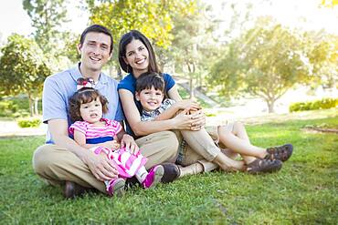 Attractive young mixed-race family portrait in the park