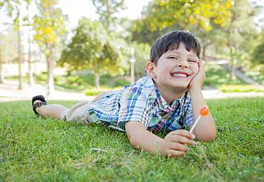 Handsome young boy enjoying his lollipop outdoors on the grass