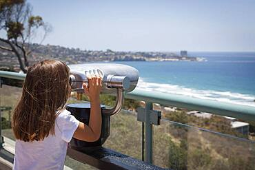 Young girl looking out over the pacific ocean and la jolla, california with telescope