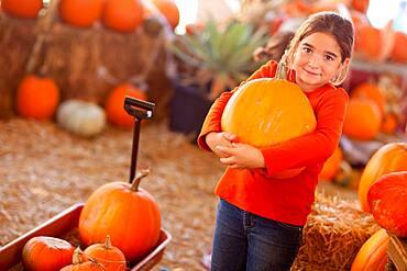 Cute girl choosing A pumpkin at A pumpkin patch one fall day