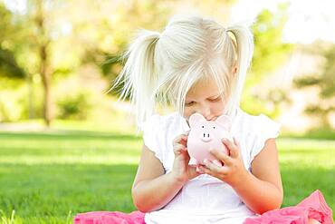 Cute little girl having fun with her piggy bank outside on the grass