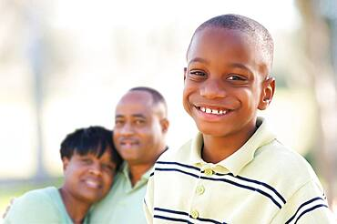 Handsome african american boy with proud parents standing by in the park