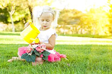 Cute little girl playing gardener with her tools and flower pot