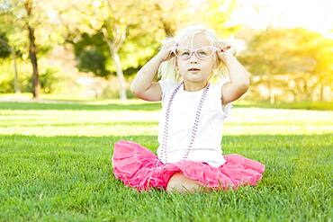 Cute little girl playing dress in the grass up with pink glasses and beaded necklace