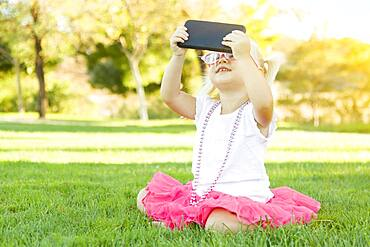 Cute little girl sitting in grass taking selfie with cell phone