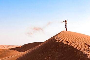 Guy playing with sand in the desert, Wahiba Sands, Sultanate Of Oman