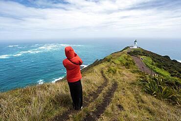 Guy infront of Cape Reinga Lighthouse, Cape Reinga, Te Rerenga Wairua, Northland, North Island, New Zealand, Oceania