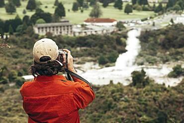 Guy with camera, Geothermal area, Redwoods Forest, Whakarewarewa, Rotorua, North Island, New Zealand, Oceania