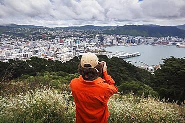 Guy with camera infront of Wellington City, Te Whanganui-a-Tara, Wellington City, Wellington, North Island, New Zealand, Oceania