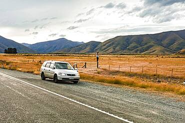 Guy with camera next to car, Omarama, Waitaki District, Canterbury, South Island, New Zealand, Oceania