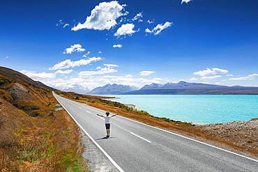 Guy on a road, Lake Pukaki, Mount Cook, Canterbury region, Mackenzie District, South Island, New Zealand, Oceania