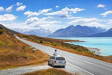 Guy on a car roof, Lake Pukaki, Mount Cook, Canterbury region, Mackenzie District, South Island, New Zealand, Oceania