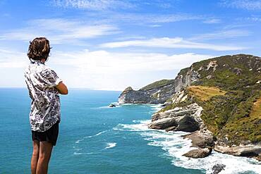 Guy at a cliff, Cape Farewell, Golden Bay, South Island, New Zealand, Oceania