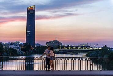 Couple standing on the bridge at sunset and kissing, Puente de Triana, view over the river Rio Guadalquivir, in the back skyscraper Torre Sevilla, Sevilla, Andalucia, Spain, Europe