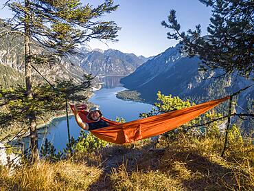 Man taking pictures of himself with mobile phone, hiker sitting in hammock with view of mountains with lake, Plansee, Ammergau Alps, district Reutte, Tyrol, Austria, Europe