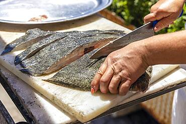 A cook cutting the fish to be barbecued in Portuguese restaurant