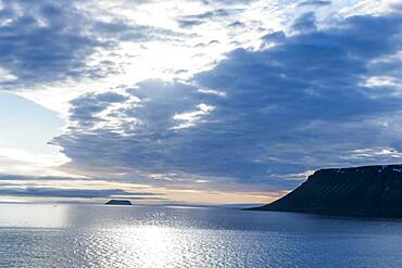 Backlight of flat table mountains covered with ice, Franz Josef Land archipelago, Russia, Europe