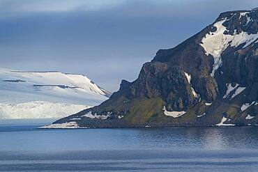 Green cliff in the glacier covered moutains of Franz Josef Land archipelago, Russia, Europe