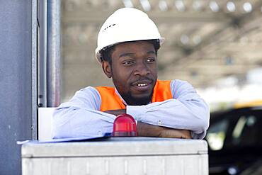 Young black man working outside as technician with helmet and safety vest, Freiburg, Baden-Wuerttemberg, Germany, Europe