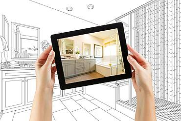 Hands holding computer tablet with master bathroom photo on screen and drawing behind