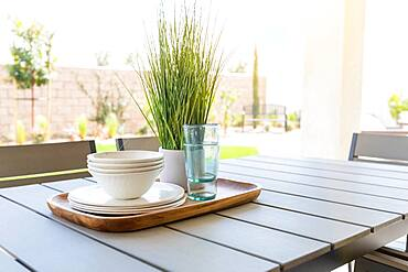Outdoor patio setting with dishes and glasses on tray