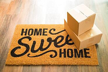 Home sweet home welcome mat on wood floor with shipment of boxes