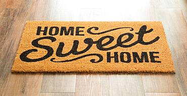 Home sweet home welcome mat on wood floor