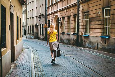 Woman in yellow t-shirt, walking by the old streets of Warsaw, Poland, Europe