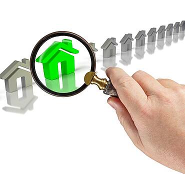 Hand holding magnifying glass up to green house in row of houses on white