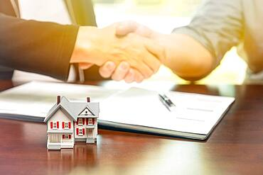 Real estate agent and customer sign contract papers and shake hands with small model home in front