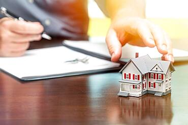 Man signing real estate contract papers and reaching for small model home in front