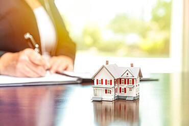 Woman signing real estate contract papers with small model home in front