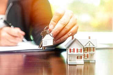 Woman signing real estate contract papers holding house keys and home keychain with small model home in front