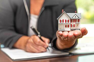 Woman signing real estate contract papers holding small model home in front