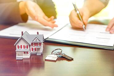 Real estate agent and customer sign contract papers with house keys and small model home in front