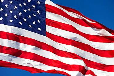 American flag waving in wind against a deep blue sky