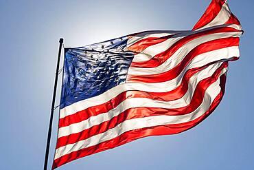 Backlit american flag waving in wind against a deep blue sky