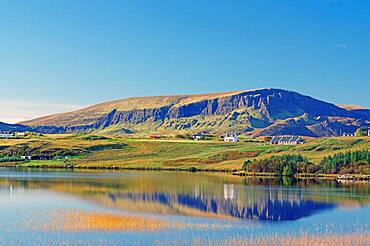 Mountains and houses reflected in a loch, autumn light, Quiraing, Isle of Skye, Hebrides, Scotland, United Kingdom, Europe