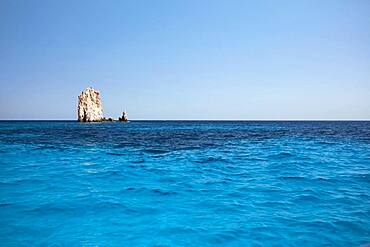Rock needle in the blue water off the coast of Polyaigos next to Milos, Cyclades, Greece, Europe