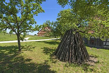 Tent-like arranged wooden poles, behind a historical farmhouse 18th century, Franconian Open Air Museum, Bad Windsheim, Middle Franconia, Bavaria, Germany, Europe