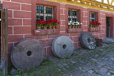 Old millstones in front of the flour mill, built 1575, extended 1601, Franconian Open Air Museum, Bad Windsheim, Middle Franconia, Bavaria, Germany, Europe